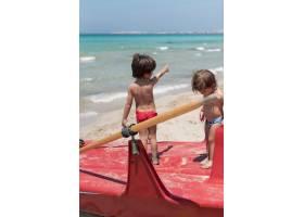 海滩上的两个孩子站在划船上_4935356