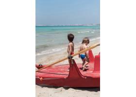 海滩上的两个孩子站在划船上_4935363