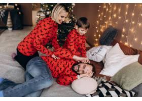 漂亮的父母和他们穿着红色毛衣的小儿子在圣_3987030