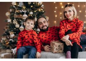 漂亮的父母和他们穿着红色毛衣的小儿子在圣_3987032