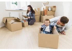 父亲和儿子和妻子一起玩耍在后台打开纸箱_3948258