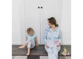 微笑的女人看着她的女儿坐在硬木地板上手_4040642