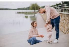 年轻的一家人带着他们年幼的孩子在湖边的公_4758355