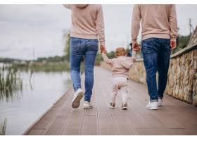 年轻的一家人带着他们年幼的孩子在湖边的公_4758356