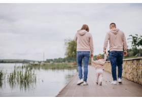 年轻的一家人带着他们年幼的孩子在湖边的公_4758357