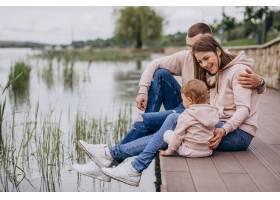 年轻的一家人带着他们年幼的孩子在湖边的公_4758359