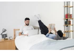 年轻的同性恋情侣躺在床上看书使用手机_4105415