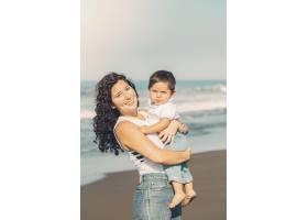 年轻的母亲在海滩上手持婴儿_4371374