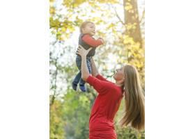 年轻的母亲抱着可爱的小男孩_5253330