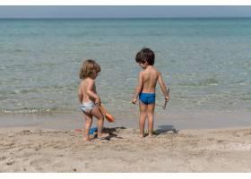 孩子们拿着玩具站在海滩上的远景_4937582