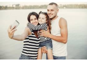带着女儿在沙滩上玩耍的一家人_4381562