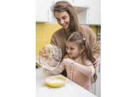 女儿和母亲把面粉放在碗里_3967131