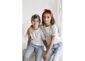 天真无邪的兄弟姐妹坐在家里的床上的肖像_5116596