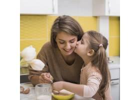 可爱的女儿在厨房做饭时亲吻母亲_3967145