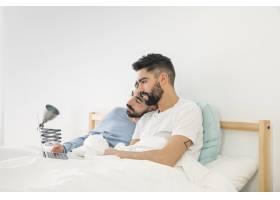 可爱的年轻同性恋情侣躺在床上看笔记本电脑_4112491