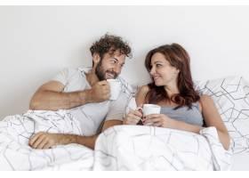 可爱的情侣在床上喝咖啡_5180847