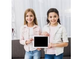 两个女孩在家中展示黑屏数字平板电脑的肖像_4105349