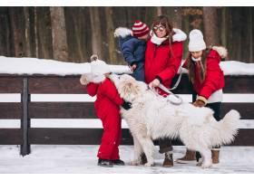 冬天母亲带着孩子和狗在外面玩耍_3964785