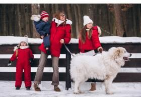 冬天母亲带着孩子和狗在外面玩耍_3964801