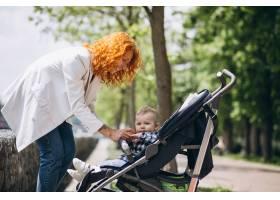 一位母亲带着她的小儿子坐在公园的一辆婴儿_5159116