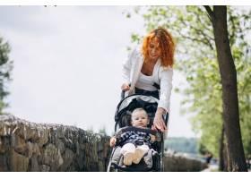 一位母亲带着她的小儿子坐在公园的一辆婴儿_5159117
