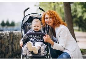 一位母亲带着她的小儿子坐在公园的一辆婴儿_5159118