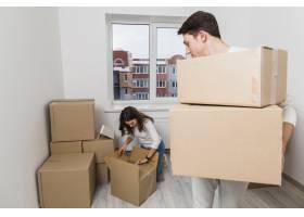 一名男子提着纸箱看着她的女朋友在新家打_3966638