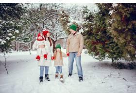 一家人带着可爱的女儿在冬季公园里_4062848