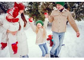 一家人带着可爱的女儿在冬季公园里_4062849