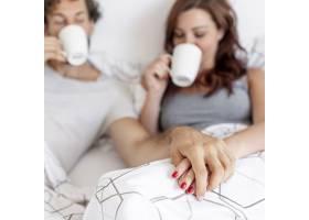 一对可爱的情侣在床上喝咖啡背景模糊_5180850