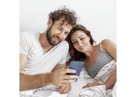 一对夫妇躺在床上看智能手机_5180863