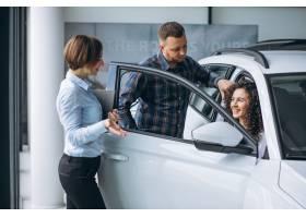 一对年轻夫妇在汽车展厅与销售人员交谈_5157695
