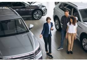 一对年轻夫妇在汽车展厅与销售人员交谈_5157712