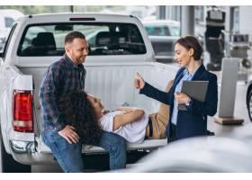 一对年轻夫妇在汽车展厅与销售人员交谈_5157720