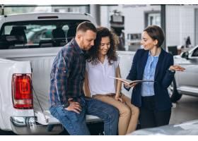 一对年轻夫妇在汽车展厅与销售人员交谈_5157721