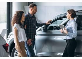 一对年轻夫妇在汽车展厅与销售人员交谈_5177611