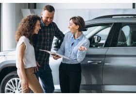 一对年轻夫妇在汽车展厅与销售人员交谈_5177623