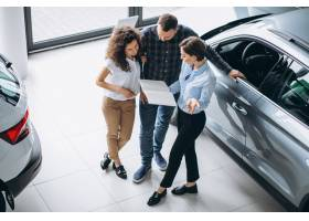 一对年轻夫妇在汽车展厅与销售人员交谈_5177628