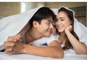 甜蜜的情侣在床上的毯子下玩耍_3395817