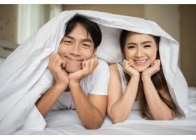 甜蜜的情侣在床上的毯子下玩耍_3395818