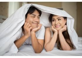 甜蜜的情侣在床上的毯子下玩耍_3395819
