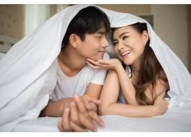 甜蜜的情侣在床上的毯子下玩耍_3395821
