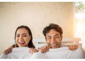 甜蜜的情侣在床上的毯子下玩耍_3397025