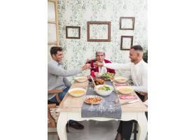 男人们在节日餐桌上碰杯_3319271