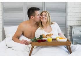 男子在飞机上接近早餐时在床上亲吻微笑的女_3524273