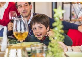 男孩在节日餐桌上吃饭_3270613