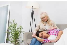 疲惫的女儿坐在沙发上睡在母亲的大腿上_3776051