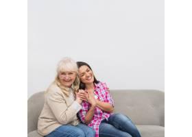 白墙衬托下坐在沙发上的母女合影_3764520