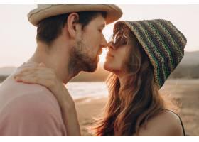 相爱的年轻夫妇站在海滩上欣赏日落的大海_3341306