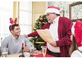 穿着红衣的老人在节日餐桌上读纸_3329707